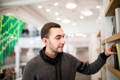 Handsome man student picking a book in a library. Male student picking a book in a library Stock Photography