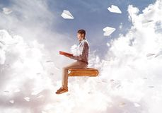 Handsome man student reading book and paper planes flying around. Young man in casual sitting on old book with one in hands Royalty Free Stock Photography