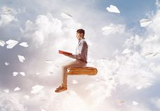 Handsome man student reading book and paper planes flying around. Young man in casual sitting on old book with one in hands Stock Photos