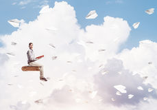 Handsome man student reading book and paper planes flying around. Young man in casual sitting on old book with one in hands Stock Photography