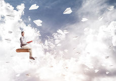 Handsome man student reading book and paper planes flying around. Young man in casual sitting on old book with one in hands Royalty Free Stock Image