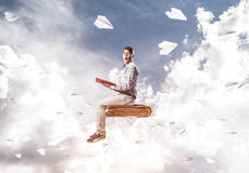 Handsome man student reading book and paper planes flying around. Young man in casual sitting on old book with one in hands Stock Images