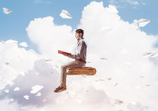 Handsome man student reading book and paper planes flying around. Young man in casual sitting on old book with one in hands Stock Image