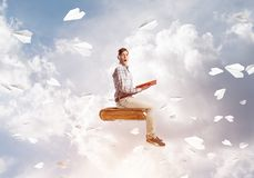 Handsome man student reading book and paper planes flying around. Young man in casual sitting on old book with one in hands Royalty Free Stock Photos