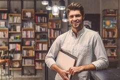 Handsome man studing in campus library. Positively about his studies. Portrait of handsome male student in university library holding laptop and smiling at Royalty Free Stock Photo