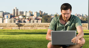 Handsome man studying or working on his computer in a urban park Royalty Free Stock Images