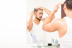 Handsome man styling his hair with gel. Portrait of an attractive young Hispanic man styling his hair in front of a mirror using some gel Stock Image
