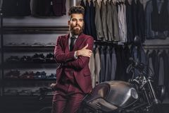 Handsome man with a stylish beard and hair dressed in vintage red suit posing near retro sports motorbike at men`s. Handsome man with stylish beard and hair stock photography