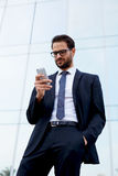 Handsome man in a stylish suit with the phone is near an office high-rise building Royalty Free Stock Image