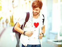 Handsome man in stylish summer clothes posing on street background Stock Images