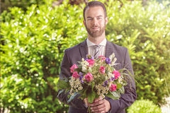Handsome man in a suit carrying flowers Royalty Free Stock Image