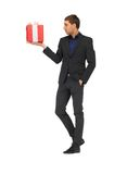 Handsome man in suit with a gift box Stock Images