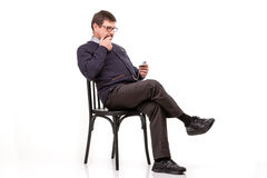 A handsome man in a suit and glasses, sits, with a pipe for smoking; White background stock images