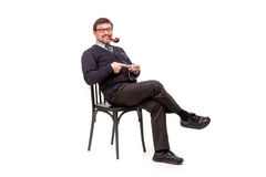 A handsome man in a suit and glasses, sits, with a pipe for smoking; White background royalty free stock photo
