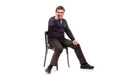 A handsome man in a suit and glasses, sits, with a pipe for smoking; White background royalty free stock photography