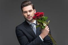 Handsome man in suit holding bouquet of red roses,. Isolated on grey stock photo