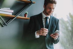 Handsome man in suit looking at his smartphone while standing stock images