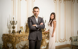 Handsome man in suit posing at classic interior with woman Stock Photos