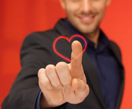 Handsome man in suit pressing virtual button. Business and love concept - handsome man in suit pressing heart-shaped virtual button Royalty Free Stock Images