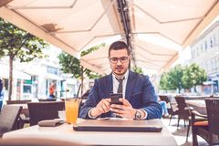 Handsome man in suit relaxing at cafe and speaking on smart phone royalty free stock photos