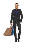 Handsome man in suit with shopping bags Stock Image