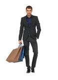 Handsome man in suit with shopping bags Stock Photography