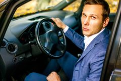Handsome successful man in suit sitting in car holding smartphone and smiling. stock images