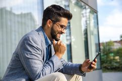 Handsome man in suit sitting in front of office building royalty free stock photo