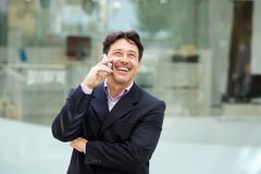 Handsome man in suit smiling with mobile phone outdoors. Portrait of handsome man in suit smiling with mobile phone outdoors royalty free stock image