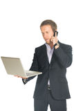 Handsome man in suit speaks on the mobile phone holding laptop Stock Photo