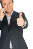 Handsome man in suit speaks on the mobile phone shows thump up Royalty Free Stock Photography