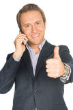 Handsome man in suit speaks on the mobile phone shows thump up Stock Photos
