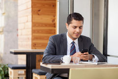 Handsome man with suit is using telephone in cafe Royalty Free Stock Photo
