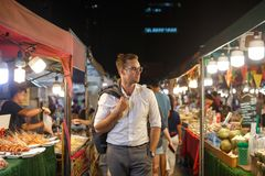 Handsome man in suit walking through a street market in Bangkok royalty free stock image