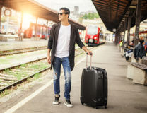 Handsome man with suitcase posing on the railway station Stock Image
