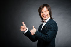 Handsome man in suite showing thumbs up in the black wall. Handsome man in studio portrait Stock Photography