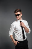 Handsome man in sunglasses and formalwear posing and looking away Royalty Free Stock Photography