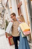 Handsome man in sunglasses with girlfriend. Holding shopping bags at street royalty free stock photography