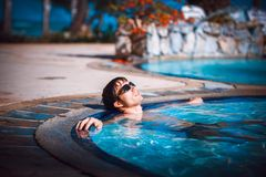 Handsome young man in sunglasses lays in swimming pool resting. happiness, summer travel vacations hotel. Royalty Free Stock Image