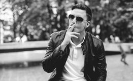 Handsome man with sunglasses in a leather jacket on the street smoking Stock Photography