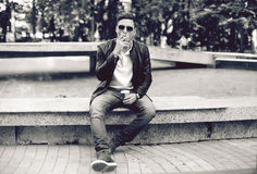 Handsome man with sunglasses in a leather jacket on the street smoking Stock Photos