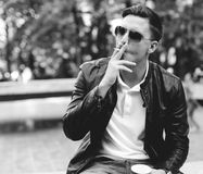 Handsome man with sunglasses in a leather jacket on the street smoking Stock Image