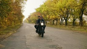 Handsome man in sunglasses riding a motorcycle with his girlfriend behind, traveling together on the asphalt road in. Forest in autumn stock video