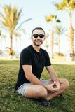 Handsome bearded man in sunglasses sitting on the grass under palms on summer vocation. Handsome man in sunglasses sitting on the grass under palms on simmer Stock Photography