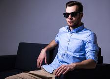 Handsome man in sunglasses sitting on sofa in dark room Royalty Free Stock Photography
