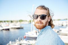 Handsome man in sunglasses visiting yacht club Stock Photo
