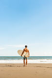 Handsome man with surfing board on spot. Royalty Free Stock Photos