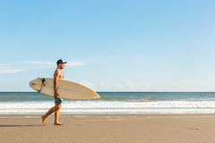 Handsome man with surfing board on spot. Royalty Free Stock Images