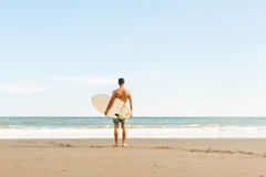 Handsome man with surfing board on spot. Royalty Free Stock Photo
