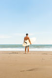 Handsome man with surfing board on spot. Stock Photo